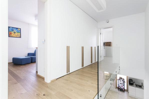 Na chodbě druhého podlaží je v nově vzniklém výklenku velká vestavná skříň bílé barvy s dlouhými dubovými madly. Přístup denního světla střešním oknem