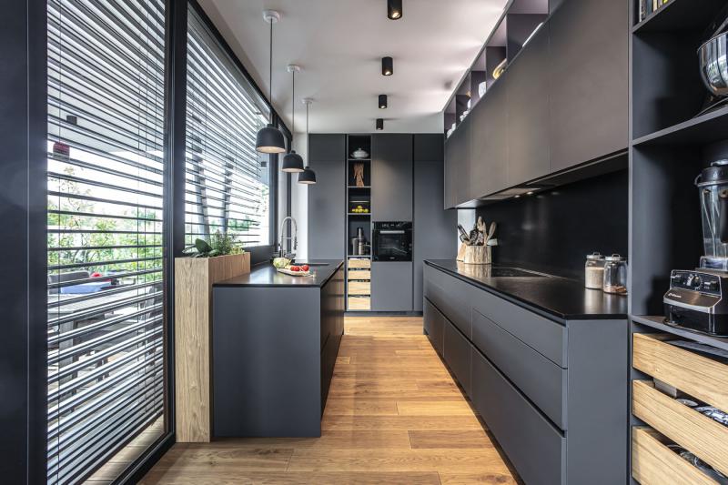 Kuchyňská linka vyrobená na zakázku je tvořena dvěma paralelními částmi s pracovními deskami z přírodního granitu a kratší úložnou stěnou s vestavěnou troubou a lednicí