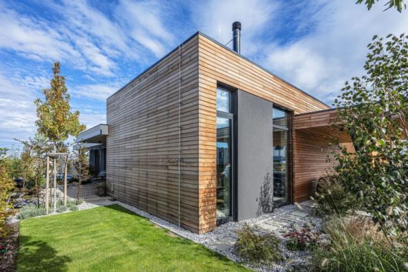 """Dům harmonicky zapadá do okolního prostředí, přísně strohé tvary a """"technické"""" materiály jsou vyváženy a změkčeny přírodním dřevěným obkladem fasády"""