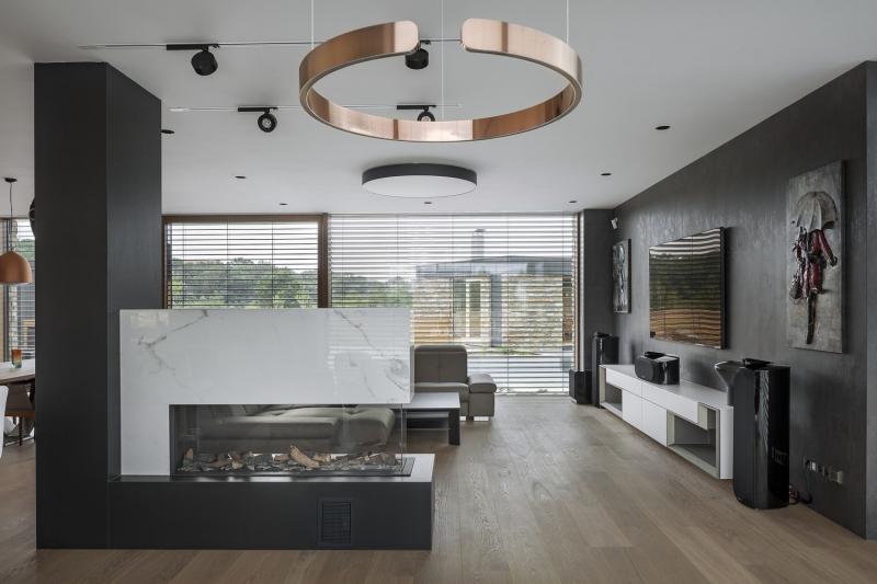 V obývacím pokoji architekti zkombinovali třívrstvou podlahu z kouřového dubu s odstíny šedé, antracitové a bílé barvy. Centrální plynový krb je obložen kompozitními deskami, které imitují bílý mramor