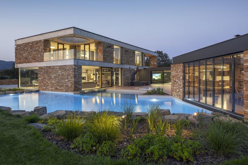 Odraz ve vodní hladině ještě zvýrazňuje architekturu založenou na jednoduchých tvarech a kombinaci plastického kamene s hladkým sklem, kovem a betonem