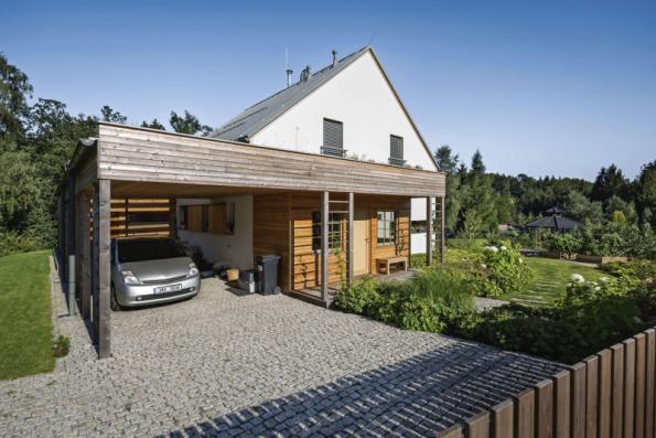 Příjezdová cesta do garáže, zpevněný povrch před přístřeškem na dřevo a přístupová cesta k domu jsou navrženy z odštěpků žulových kostek uložených ve štěrkovém loži (okraje ploch v betonovém základu)