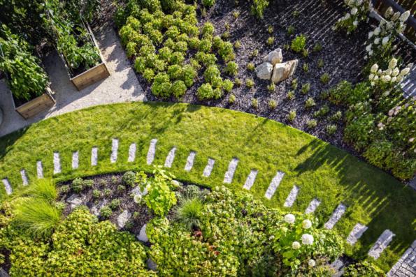 Od hlavní přístupové cesty se jihovýchodním směrem odděluje cestička z kamenných šlapáků (liberecká žula), která míří obloukem kolem okrasných výsadeb pod okny kuchyně přímo na hlavní jižní terasu s bylinkovými záhony