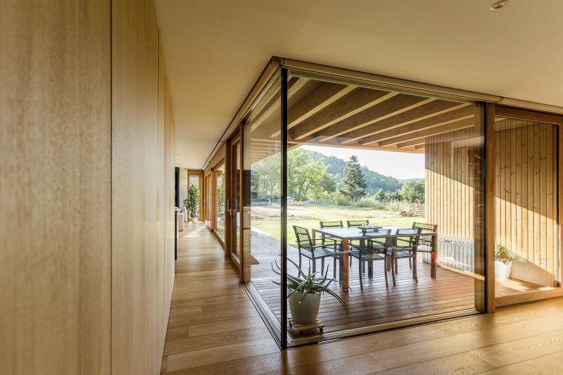 Pohled ze studovny na terasu. Dům je z jedné strany téměř plně prosklený, což pocitově zvětšuje jeho interiér, příjemně ho prosvětluje a zároveň propojuje s exteriérem