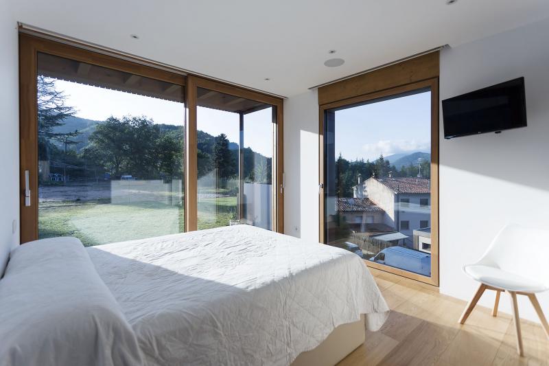 Ložnici Clary a Carlese obklopují velká prosklená okna, která rámují výhled do kraje a nabízejí během roku proměnlivé obrazy