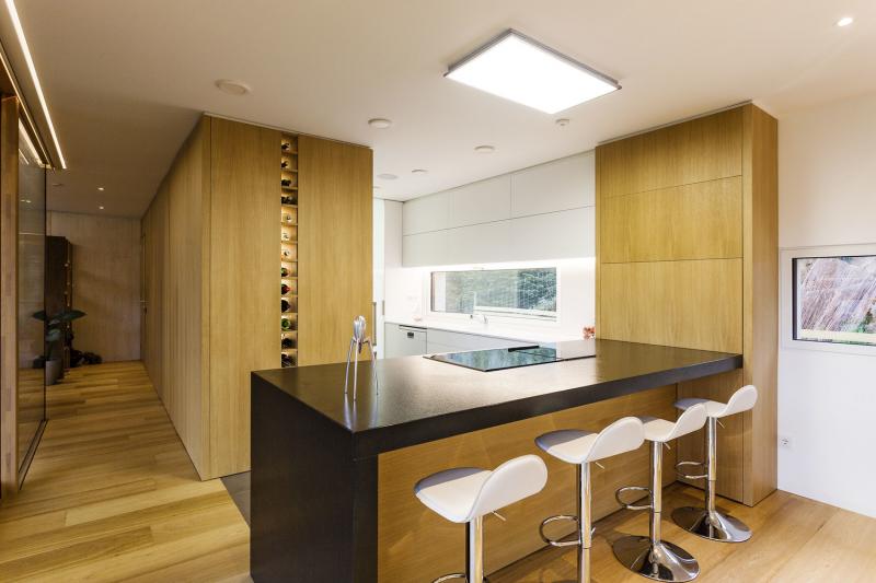 Kuchyňský pult je nejen srdcem kuchyně, ale zároveň ovládacím centrem systému Loxone. Kuchyni a chodbičku odděluje skříňová stěna, která je částečně přístupná z obou stran