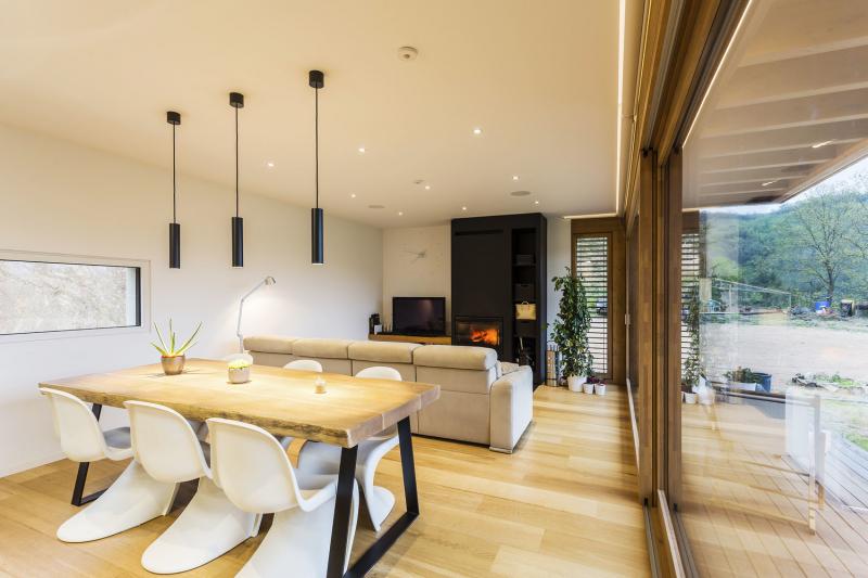 Velký masivní dřevěný stůl dodává jídelně rustikální atmosféru. A že je v domě zdravé klima, to dokazují rostliny, které zde vyloženě prospívají, jako například vzrostlá šeflera vedle krbu