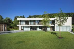 Zadní fasáda podlouhlé stavby se v obou výškových úrovních otevírá směrem do zahrady díky posuvným systémům (Schüco ASS 77 PD.SI