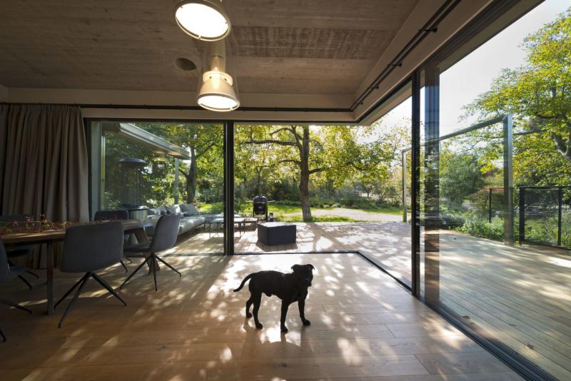 Společný obývací prostor prosklenou stěnou přechází ven do exteriéru. Atypické řešení bez rohového sloupku bylo možné realizovat díky masivnímu rohovému železobetonovému překladu. Dubová podlaha bezbariérově přechází v dřevěnou terasu, práh je skryt v podlaze.