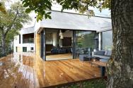 Hlavní obytná část domu je orientována na dřevěnou terasu ukrytou mezi stromy. Navazuje na nejvýše položenou část zahrady, kde je také nejvíce soukromí