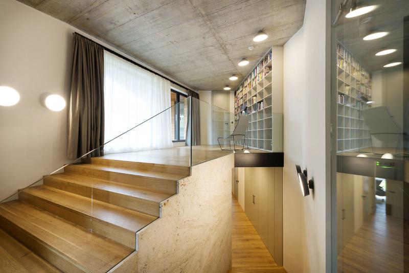 Společný obývací prostor se otevřeně propojuje s chodbou ve spodním podlaží a s knihovnou, z níž se vstupuje do ložnice rodičů