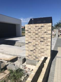 Ve venkovní části domu se provádí zděný plot z pálených cihel Terca. Základ byl proveden ze ztraceného bednění vylévaného betonem. Zmonolitněná konstrukce nese vyzdívaný plot a je podkladem pro nosnou část venkovní příjezdové brány vstupní branky (zdroj: Wienerberger )