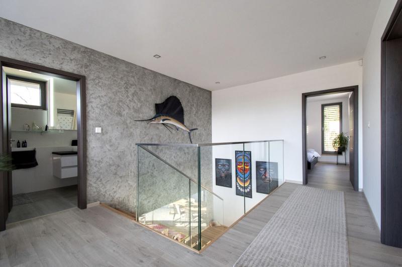 Skleněná stěna prochází z přízemí až do prvního patra, kde je zakončená hliníkovou lištou a tvoří zábradlí galerie