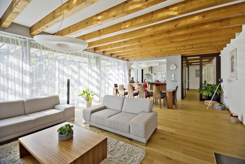 Pohled do společného obývacího prostoru vyznívá díky přiznaným stropním trámům a dubové podlaze útulným a zatepleným dojmem. Architekti sem záměrně vybrali světlé neutrální barvy posilující harmonický dojem. Po technické stránce bylo v dřevostavbě náročným úkolem vytvořit dokonale rovný podklad pro dlouhou prosklenou stěnu z HS portálu, i to se ale podařilo dobře zvládnout