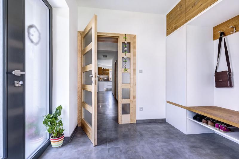 Jedna strana šatní skříně přechází v prostor pro pověšení oděvů s deskou pro sezení při obouvání a otevřený botník. Bílý povrch je vtipně prostřídán přírodním odstínem dřeva