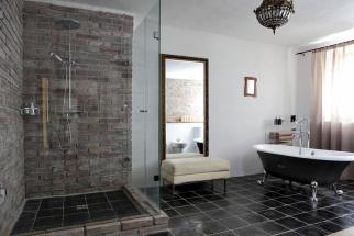 Kombinace čedičové dlažby, režného zdiva a hladké bílé omítky vytváří zcela originální koupelnu. Vana na nožičkách imituje historické litinové vany a spolu se starým zrcadlem sem přirozeně zapadá. Design Martina Schultes