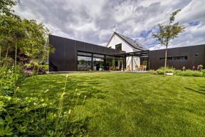Nové přístavby architekti odlišili od původní části domu moderním industriálním výrazem, především černým obkladem z hliníkových desek a plochými zelenými střechami. Společná obývací část je lemována dřevěnou terasou, která navazuje na zasklenou pergolu s venkovním sezením