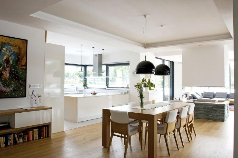Kombinace svítidel, jejichž tvar byl navržen pro tento dům, otevřeného prostoru, pečlivě zvolených pastelových tónů stěn a pronikajícího denního světla vytváří přívětivě laděnou atmosféru interiéru