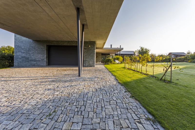 """Obytná část je orientována na prosluněné strany, zároveň se architekti snažili omezit vizuální kontakt se sousedy. K domu vede snadný příjezd po dlážděné žulové cestě, klidová zóna se nachází v """"závětří"""" za obývacím pokojem"""