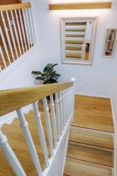 Nástup na schodiště je součástí obytných prostor v přízemí, a proto si drží jeho ráz. Osvětlení v dřevěné liště je stejné jako v obývacím pokoji a doplňuje atmosféru bytu