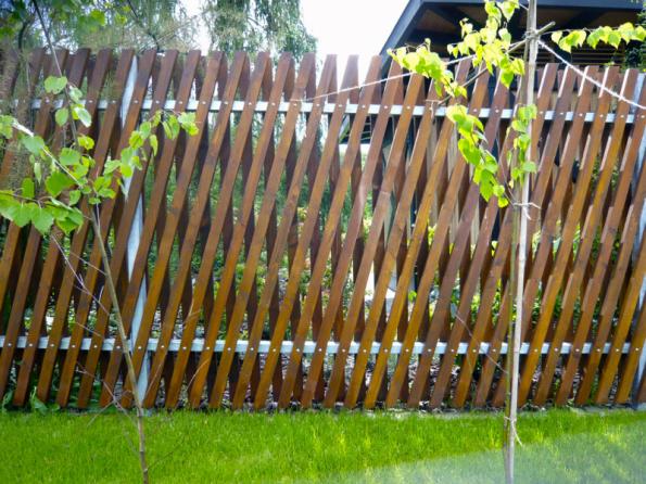 Orientace dřevěných latí vzhled plotu výrazně ovlivní. Zde se latě uložily pod úhlem ve dvou řadách, takže zajišťují soukromí, ale zároveň zahradu neizolují od okolí