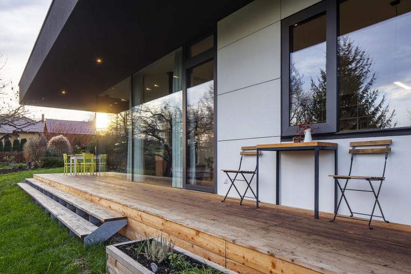 Dřevěná terasa lemující dům ze dvou stran je přesahem střechy chráněna před sluncem a deštěm