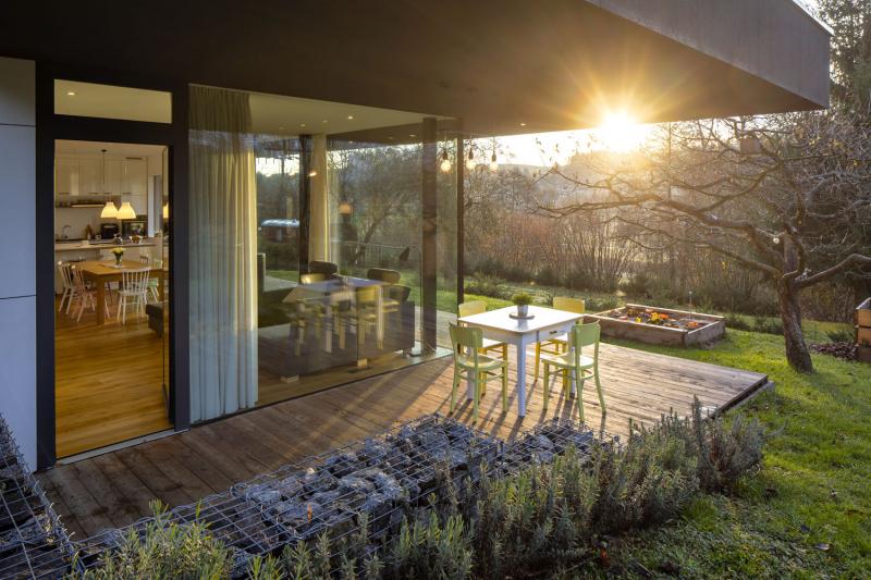 Prosklené stěny vpouští do domu dostatek světla a otevřením prostor získá i vzdušnost. Přesah střechy v horkých dnech interiér chrání před přehřátím, na jaře a na podzim jej naopak sluneční paprsky prohřívají