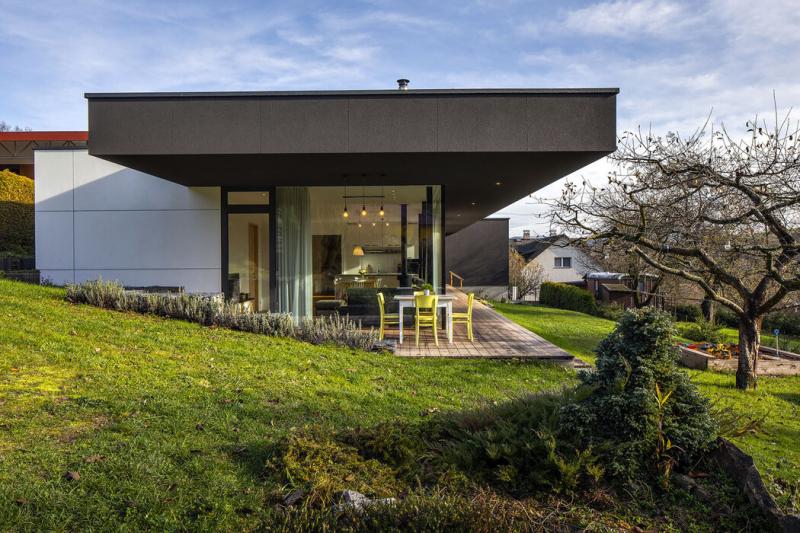Prosklené stěny otevírají centrální obytný prostor na terasu orientovanou západním a jižním směrem. Mírné zapuštění stavby do svahu umožnilo přímé napojení terasy na této straně na terén zahrady
