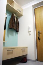 Barevná obkladová deska doplňuje praktické členění předsíňové stěny. Nábytek působí vzdušně a přitom obsahuje dostatek úložných prostor (Studio Evalofa)