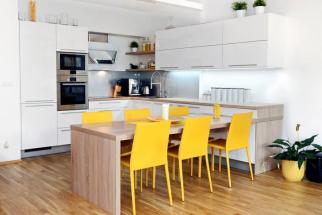 V sestavě ve tvaru U stůl tvoří předěl mezi kuchyní a obývací částí, v přímé návaznosti na kuchyňskou desku je možné ho využít i jako pracovní plochu, realizace JN Interier, www.jninterier.cz