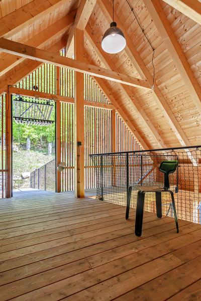 Pohled z horního patra stodoly ukazuje, jak tenká vizuální bariéra odděluje tento prostor od okolního lesa. Zde si můžete chráněni před deštěm a větrem užívat horského vzduchu