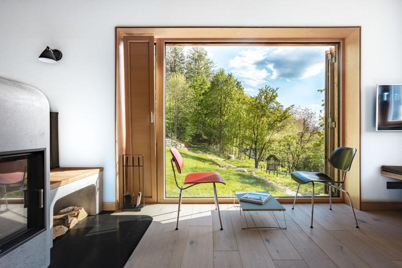 Jedním z důležitých prvků koncepce domu je maximální propojenost s exteriérem. V popředí překližkový solitérní nábytek legendární značky Nils Holger Moormann