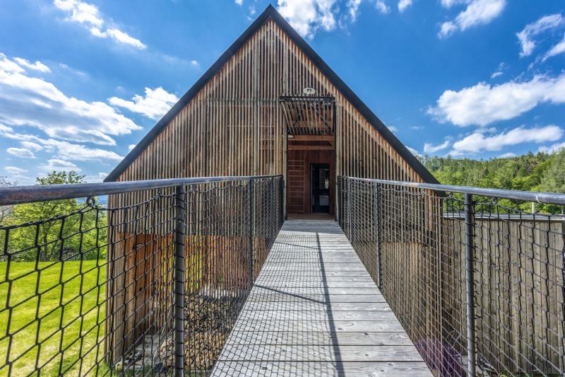 V horní, půdní části stodoly, která je otevřená do lesa, lze spát pod širákem, aniž by na vás pršelo, dole je prostorný dřevník. S lesem dům propojuje lávka v úrovni podkroví