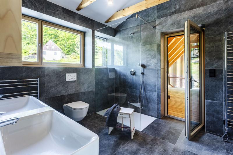 """Místo původně navrhované vany nechal majitel instalovat dvojité umyvadlo a sprchový kout. Tmavý obklad stěn a podlahy """"prosvětluje"""" sádrokarton a krovní kleštiny"""