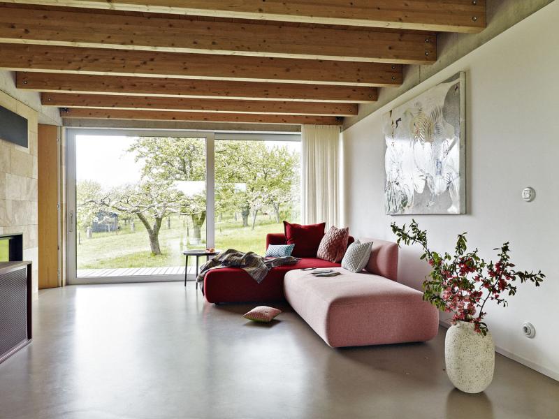 Klienti si s architekty rozuměli v základní koncepci, v konstrukčním řešení stavby i ve výběru materiálů. Nebáli se investovat do poměrně drahých oken a počkat si na dokončení interiérů. Stropy jsou dřevěné, na podlahách epoxidová stěrka. A v hlavní obytné místnosti pískovcová stěna, která dobře akumuluje teplo z kamen