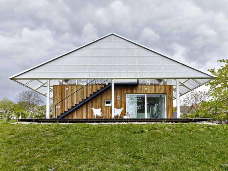 Dům s modřínovou fasádou chrání lehká střecha s velkými přesahy nad terasou – u průčelí je přesah střechy metr a půl, z boku tři metry. Ukázalo se, že pobyt na terase pod polykarbonátem je i v létě příjemný. Terasu majitelé využívají jako běžný komunikační prostor díky velkým posuvným oknům