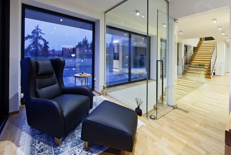 Pracovna, oddělená od hlavní obývací části stěnou z čirého bezpečnostního skla, má stálé optické propojení jak s interiérem, tak se zahradou. Samozřejmě i zde dominuje impozantní výhled