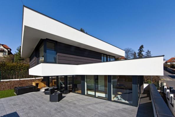 Kompozice domu maximálně těží z polohy pozemku v jihozápadním svahu. Dvě navzájem pootočená prosklená podlaží reagují na pohyb slunce a také na výhledy do okolí. Přidanou hodnotou se stal atraktivní dynamický tvar