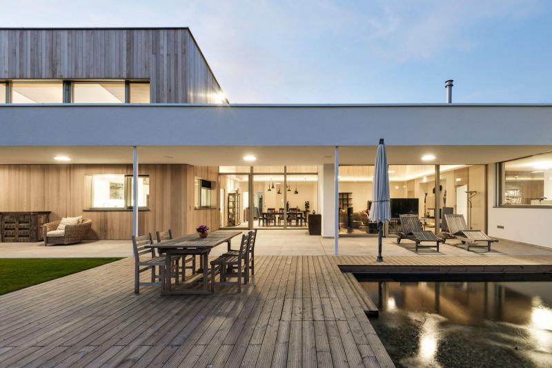 Bezbariérové propojení interiéru a exteriéru probíhá z obývacího pokoje přes krytou terasu až na dřevěnou palubu v okolí bazénu a na trávník