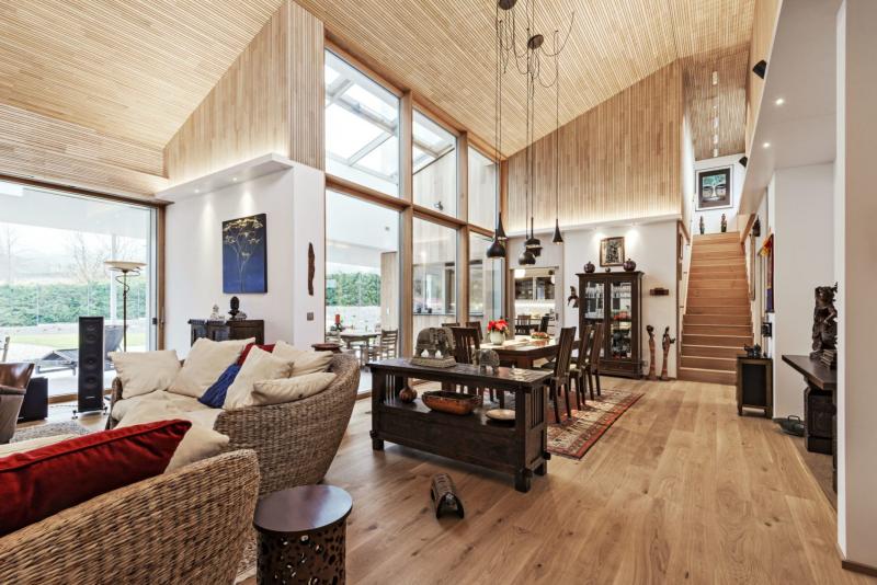 Společný obývací prostor s šest metrů vysokým stropem okouzluje impozantní atmosférou podobnou hlavní lodi staré katedrály. Strop a část stěn jsou obloženy cedrovým dřevem jako na fasádě. Do moderního interiéru si majitelé vybrali masivní dřevěný nábytek v etno stylu