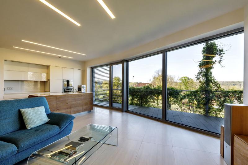 Obývací pokoj je bazbariérově propojen s terasou. Čelní prosklená stěna se skládá z velkoformátových polí, která kopírují zakřivení fasády