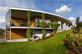 Obloukové zakřivení hlavního průčelí přináší panoramatické výhledy a dodává stavbě výrazně dynamický vzhled