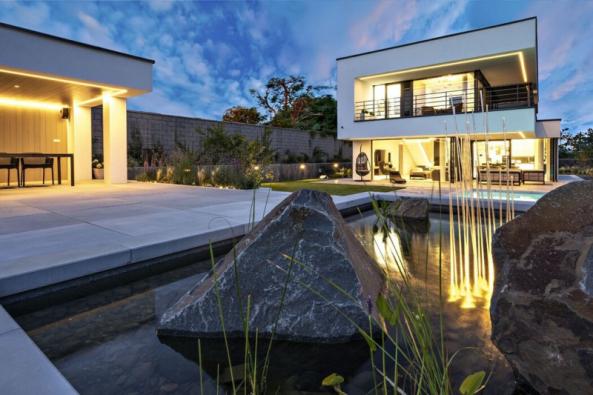 """Provázanost domu se zahradou nejvíce vynikne při večerním osvětlení. Celý systém tvoří programovatelnou scénu s efektními prvky, jako je například speciální """"svítící rákos"""" – svítidla Reeds od italského výrobce Artemide, umístěná ve vodě a na trávníku"""
