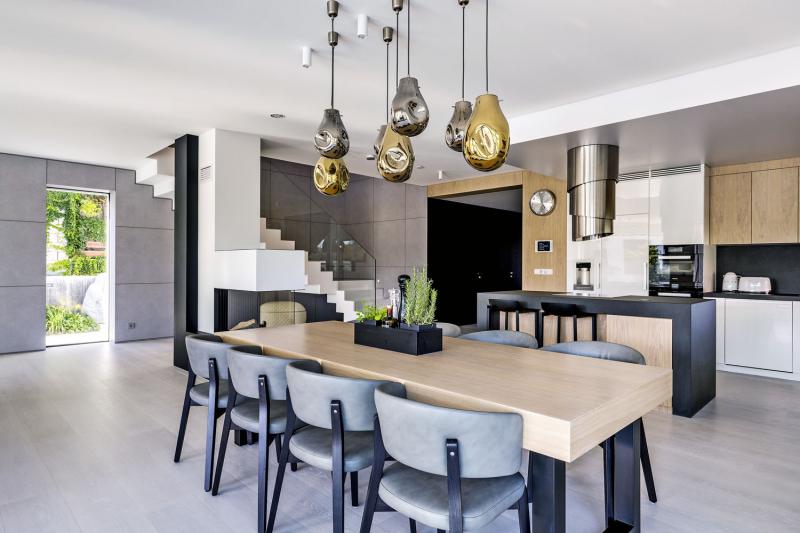 Šedé tóny betonu jemně kontrastují s hřejivými odstíny dřeva. Na jídelním stole, barovém pultu a kuchyňské lince byl použit přírodní dub, na podlaze dub bělený, černě zbarvené dřevo je dub čpavkovaný