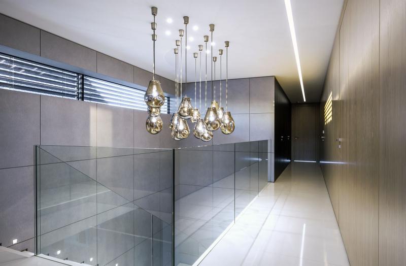 Svítidla značky Boma se opakují ve schodišťovém prostoru, obloženém velkoformátovým betonovým obkladem. Zábradlí z čirého tvrzeného skla propouští světlo a netvoří v interiéru žádnou optickou bariéru