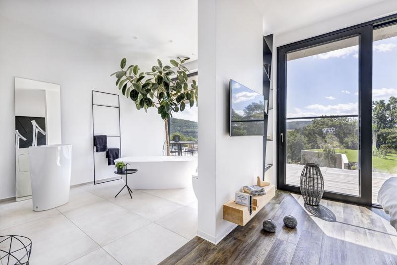 Prostorná koupelna volně navazuje na ložnici a nabízí hned několik skvostných designových kousků: solitérní vanu, volně stojící umyvadlo, závěsnou skříňku se škvírou pro kabel atd.