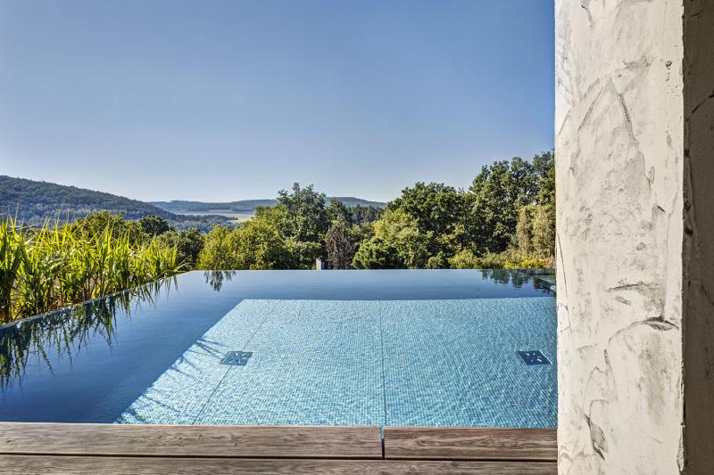Pohled z terasy do kraje přes horizont průzračné vody v nerezovém bazénu je skutečný zážitek. Voda v bazénu je vyhřívaná tepelnými čerpadly