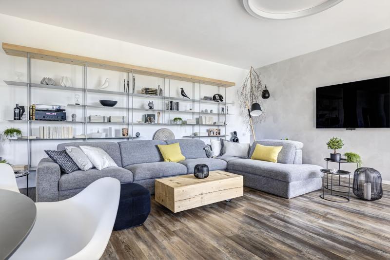 Dominantou obývacího pokoje je kovová knihovna vyrobená na zakázku. Všimněte si, že dekorace barevně ladí s pojetím interiéru. Pozornost ale poutá i stolek z poctivého masivního kusu dřeva