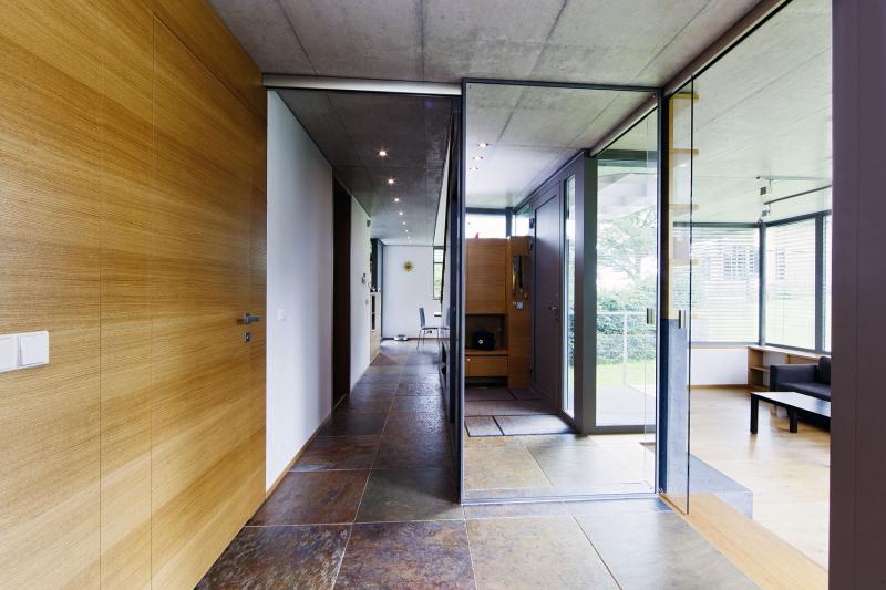 Volné průhledy a světlo ze všech stran – tento záměr architekta je patrný již při vstupu do domu. Z předsíně je vidět do obývacího pokoje a také podél schodiště až dozadu do jídelny. Posuvná zrcadlová plocha zůstává prakticky stále otevřená