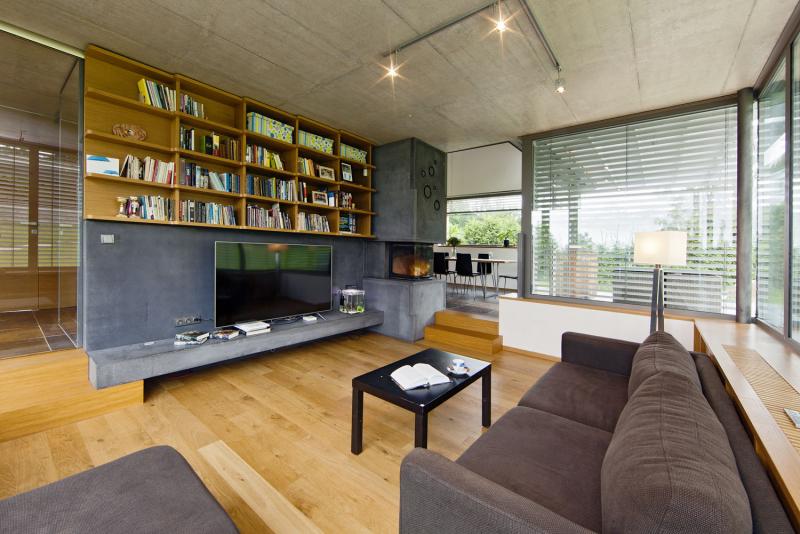 """Design interiéru je založen na kombinaci přírodního dubu a šedých odstínů betonu a kovu. Ústřední krbové těleso je obloženo šedými PREFA panely a plechem s šedým práškovým lakem, v němž jsou vyřezány ozdobné kruhové otvory s funkcí větrací mřížky. """"Polička"""" na televizi je masivní betonový prefabrikát tunové váhy"""